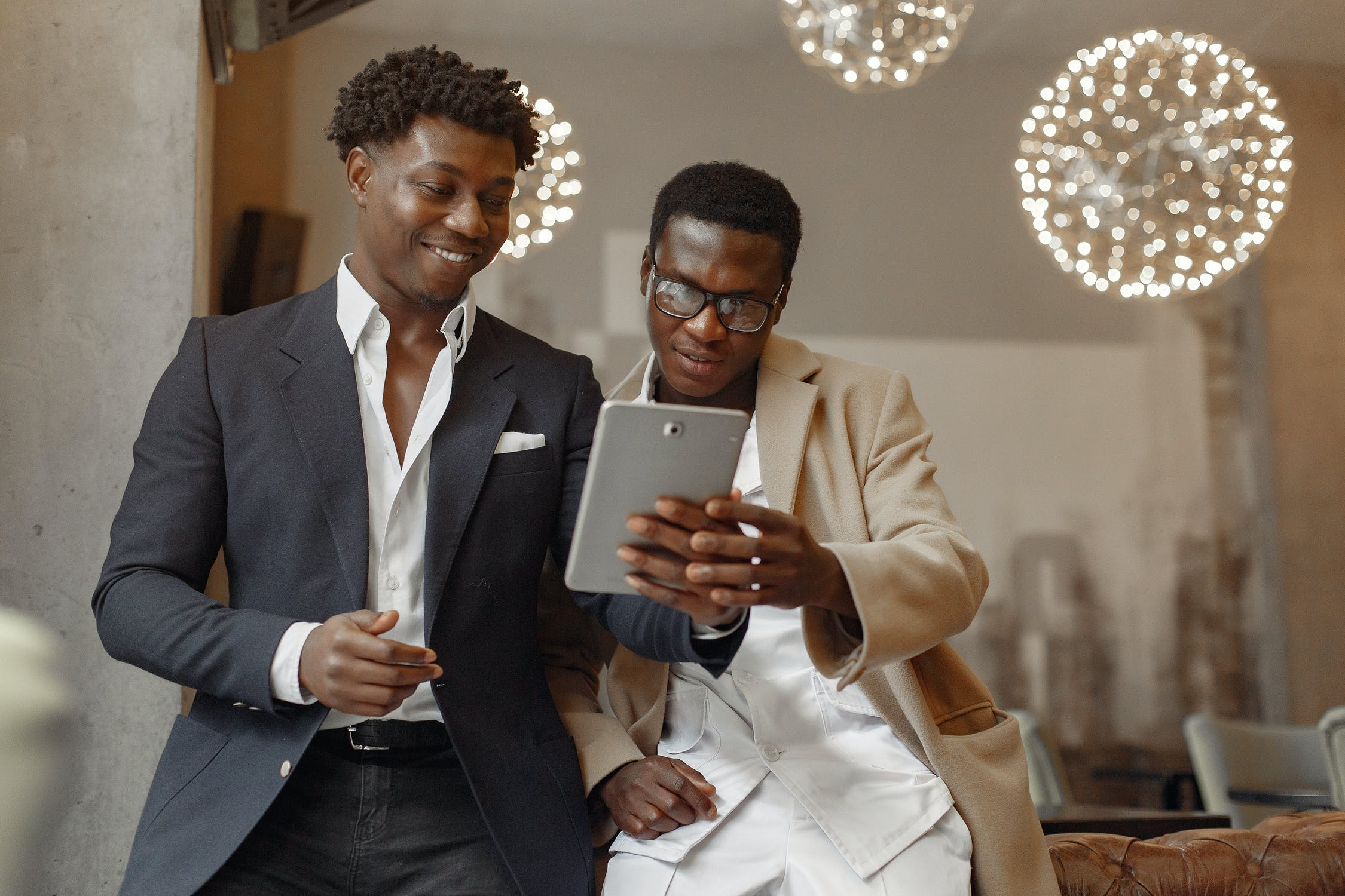 Two men in suits looking at a tablet