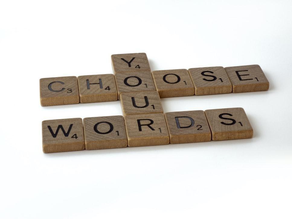 "Scrabble tiles spelling ""choose your words""."