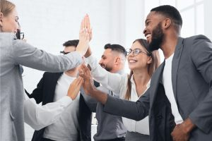 Team achievement, diverse business people giving high five at meeting