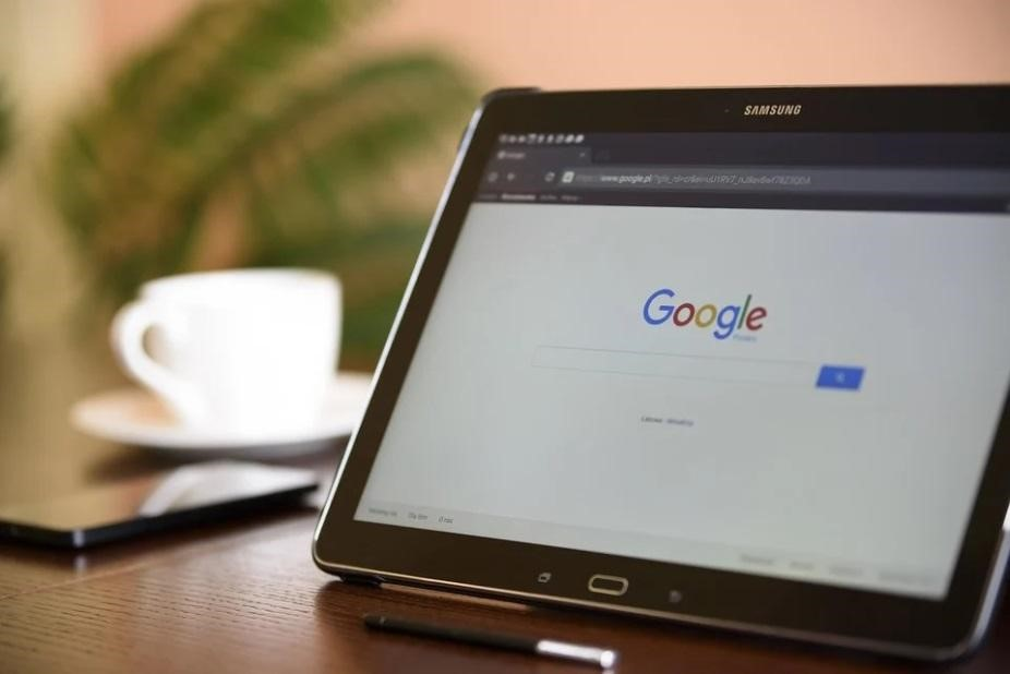 A black tablet on a desk, displaying Google's search engine page.